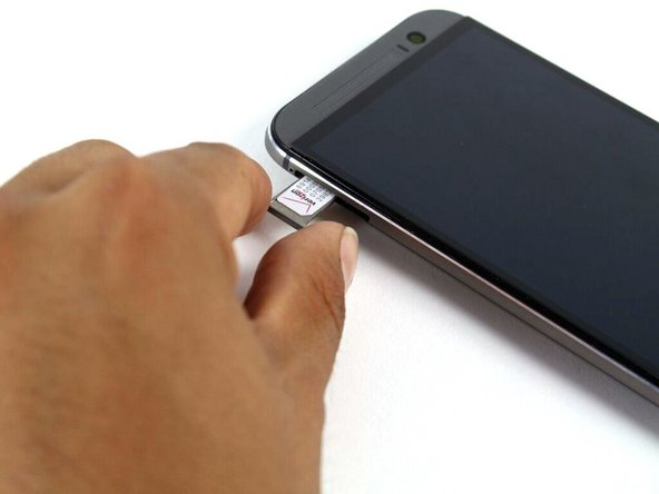Image 1/1: When reinserting the SIM card, ensure that it is in the proper orientation relative to the tray.