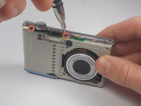 Remove the three black screws connecting the chrome frame to the camera.