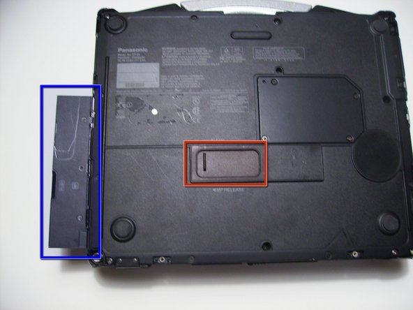 Image 1/1: Open the optical drive bay by sliding its latch to the right.