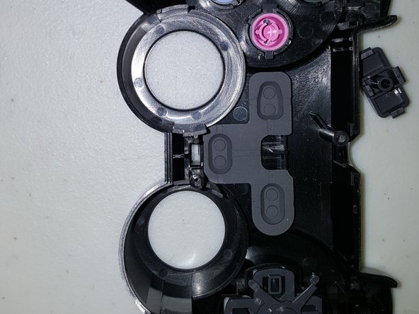 In the first picture, you can see the bottom of the top shell of the Dualshock 2 controller. In the second one, you can see the joysticks without the rubber part.