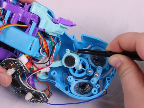 Using the angled tweezers tool, disconnect the spring that is attached to the nose from the lever.