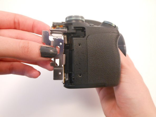 Image 2/2: Gently remove the silver piece from the side of the camera. It should come out easily using your fingers.