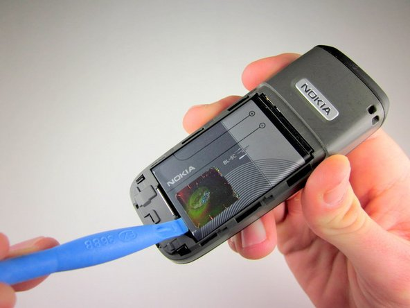 Use a plastic opening tool (or your finger) to gently pry the battery out of the battery slot on the back of the phone.