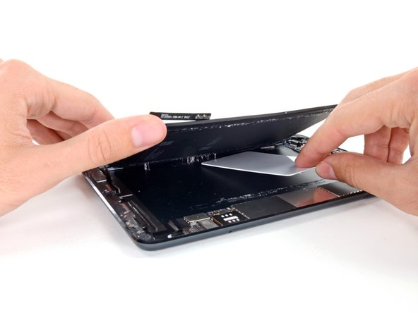 While lifting the right side of the battery up with one hand, use a plastic card to cut any adhesive still holding the battery down to the rear case.
