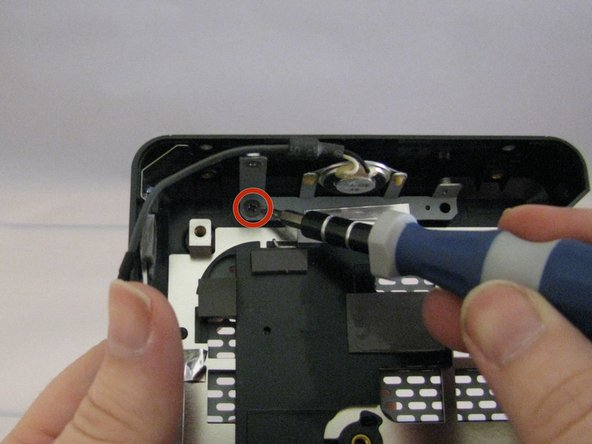 Remove the 5mm Philips #0 screw securing the speaker mounting bracket to the case.