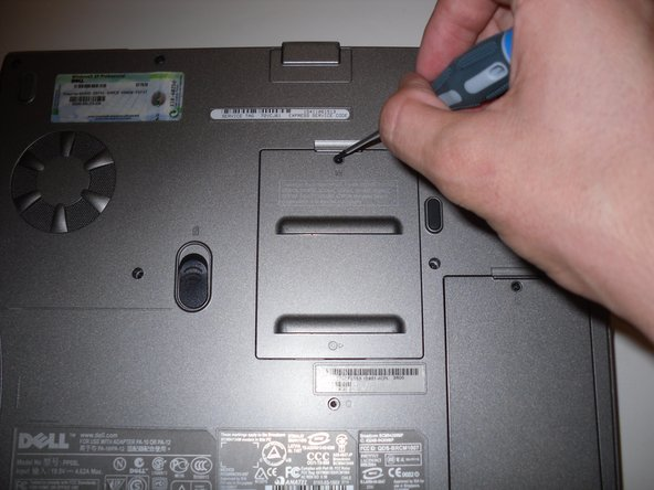 Take the screw driver and carefully unscrew the screw that is located above the M in order to remove the panel.