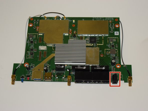 Image 1/2: The power port on the top side is in a rectangular black casing.