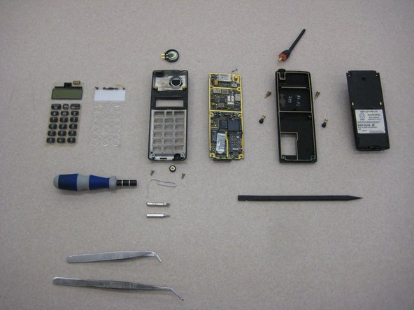 From left to right, top to bottom: Speaker, antenna, LCD screen, keypad, keypad support skeleton, front casing, circuit board, back casing, battery, screwdriver handle, paperclip, Torx T6 bit, SP2.6 U-bit, plastic pry bar, and two sets of tweezers.