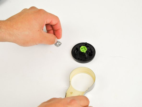 "Remove the gray silicone cover to expose the backside of the bright green, round ""X"" button."