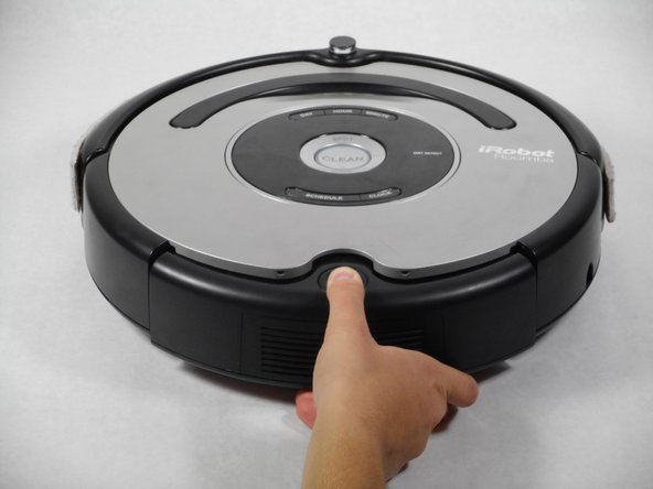 Press the black circular button on the back end of the Roomba and pull the bin out towards you to remove the vacuum bin.