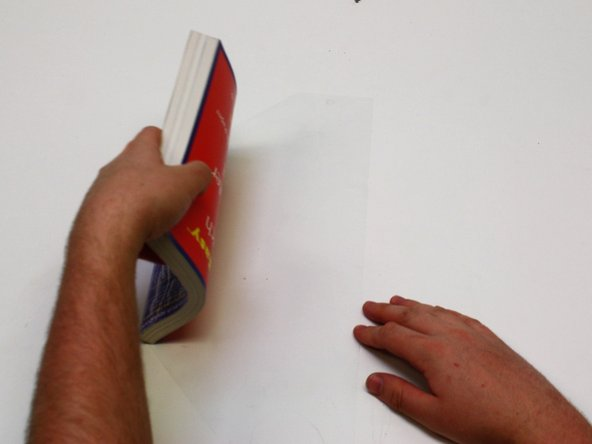 Repeat motions from step 7 and slowly roll your book cover onto the laminate film.