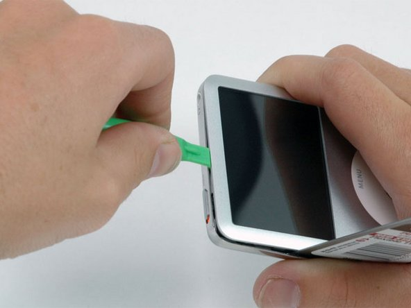 Image 1/1: Near the headphone jack, insert a plastic opening tool into the seam between the front and back of the iPod.
