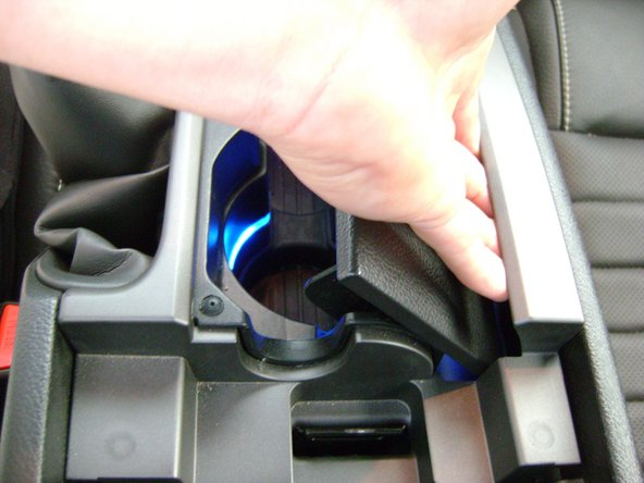 Grip the right side of the console and pull up towards the passenger seat to remove it.