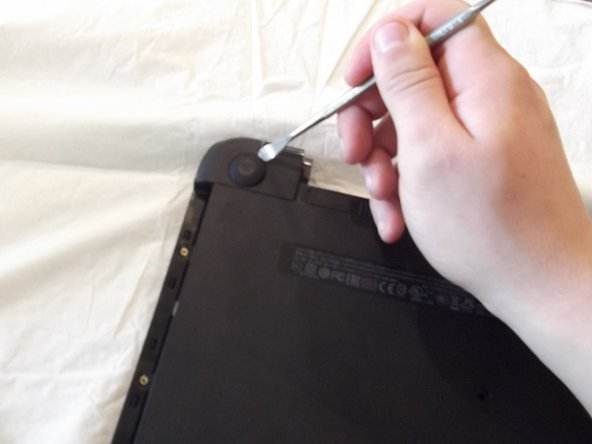 Using a spudger to remove the rubber bumpers located at the top left and top right of the laptop.