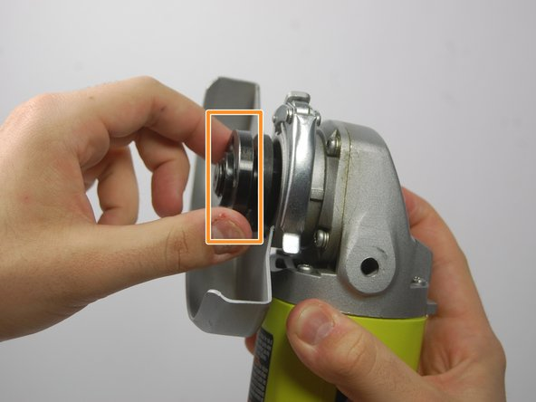 Image 3/3: With the spindle lock button held down, use the wrench provided to loosen the clamp nut. Once loose, you can use your fingers to unscrew the nut completely