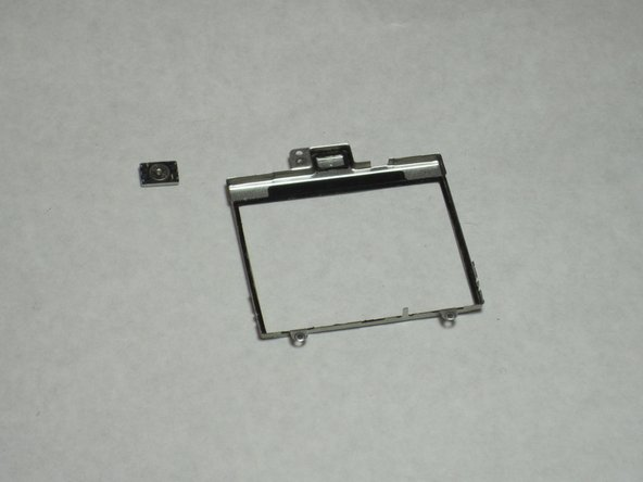 The speaker is connected to the display frame by a ring of adhesive foam (visible in second picture). By removing the speaker, this foam is torn. However, the speaker sticks quite well to the frame without reapplication of any adhesive.