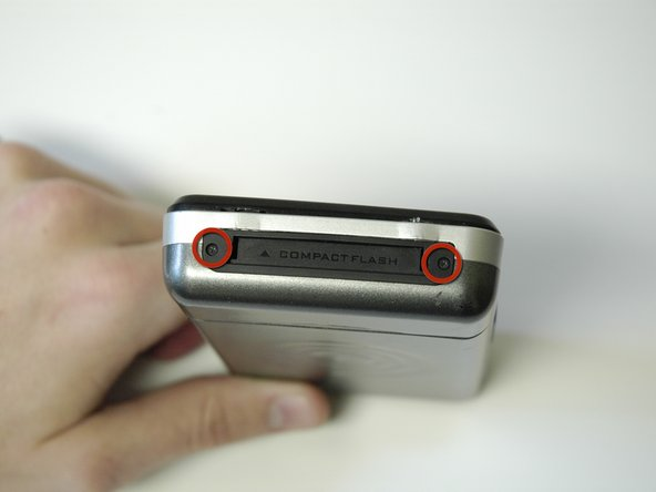 Remove the 2 screws (3.5 mm) on the Compact Flash insert, located on the left hand side, with a Phillips #000 screwdriver.