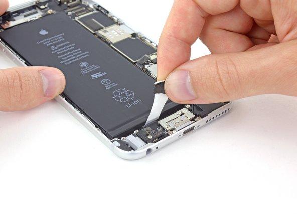 バッテリーから丁寧に接着タブを上向きに引っ張ります。バッテリーとリアケースの間から接着タブをゆっくりと取り出します。