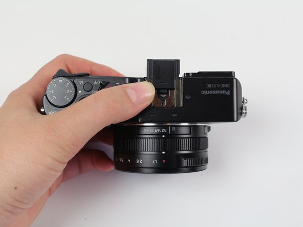 Remove the small metal insert that rests beneath the black plastic piece by pulling outward, away from the lens side of the camera.