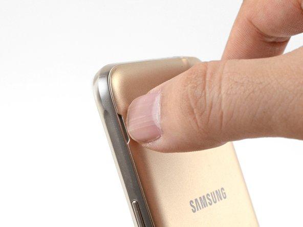 Inserta una uña o el extremo plano de un spudger en el orificio a la izquierda de la cámara trasera.