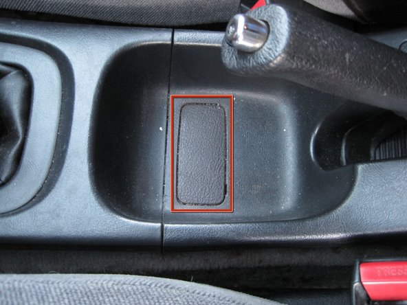 Insert a small flathead screwdriver into the notch at the driver's side rear corner of the screw cover directly below the parking brake lever and pry it off.