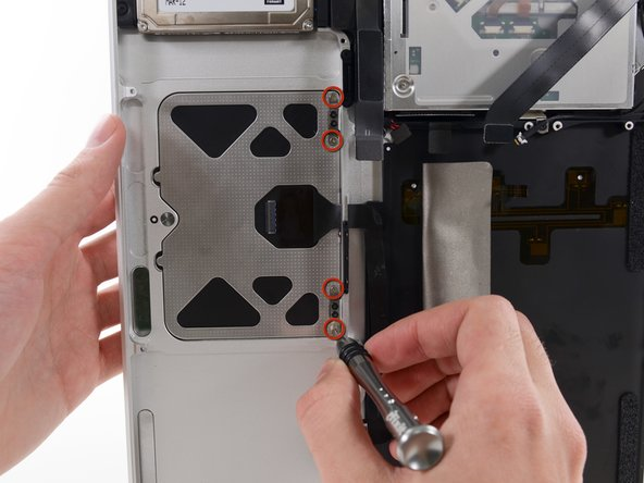 Image 1/1: Remove the four silver 1.3 mm Phillips #00 screws from the trackpad spring brackets.