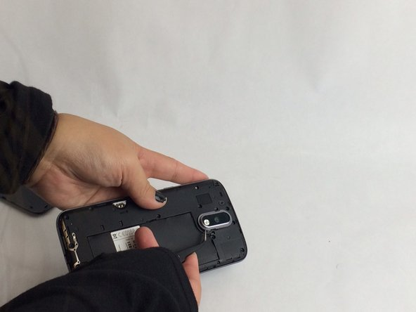 Remove the gray plastic surrounding the camera lens with a pair of tweezers.