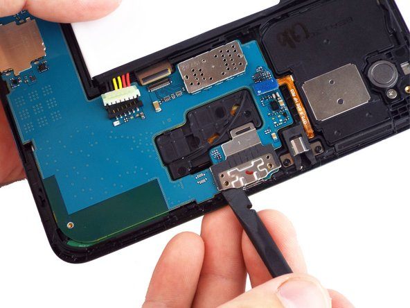 Then use the spudger tool to remove the USB port shield.