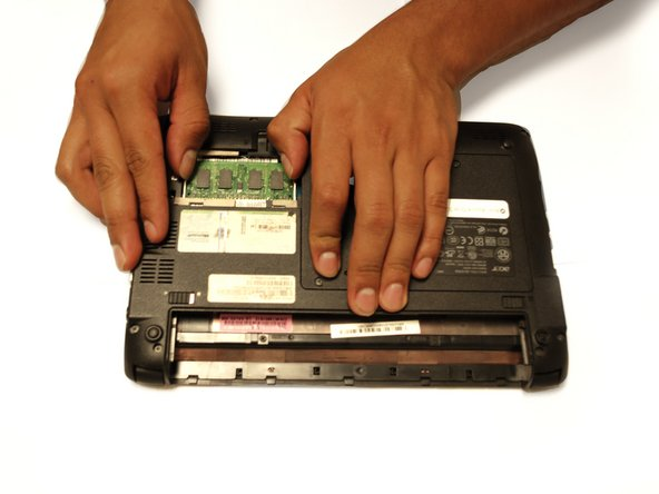 Using two fingers, gently spread the latches on the sides of the RAM card until the RAM card props up.