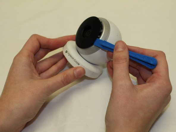 Wedge the plastic opening tool under the black circle lens to gently pry it off.