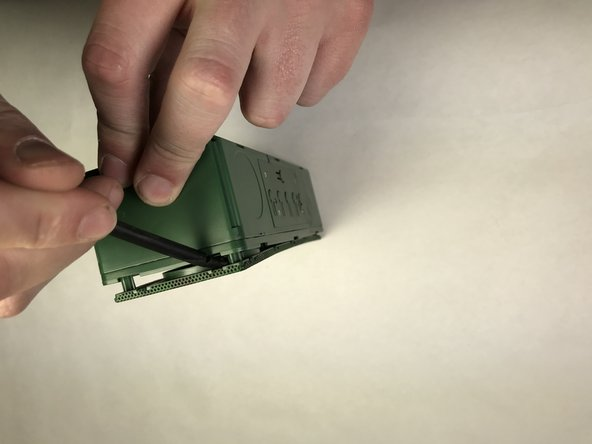 Using hands or a spudger, pry the front side of the plastic shielding (side opposite of power, control, and auxiliary port cover) from the device.