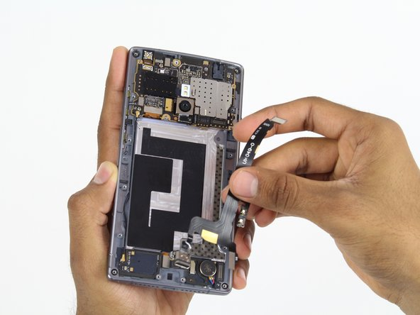 Image 3/3: Once the charging port is free from the frame, use your fingers to remove the charging port the rest of the way.