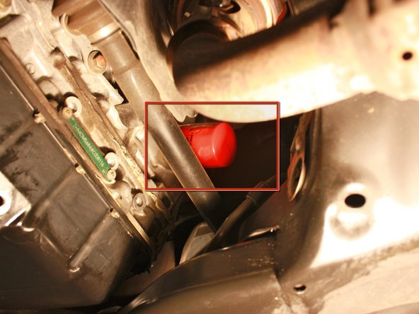 Identify the oil filter and place drip pan under the oil filter to catch falling oil.
