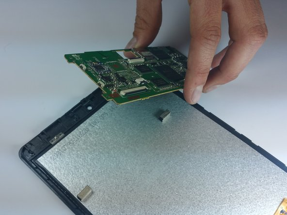 Image 2/2: Carefully lift the motherboard off of the device and remove.