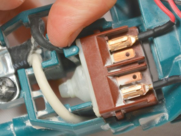 Pull back the plastic clip and pull the internal switch up and out of the cavity.
