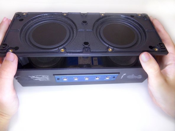 Lift the black covering off of the speaker using both hands.