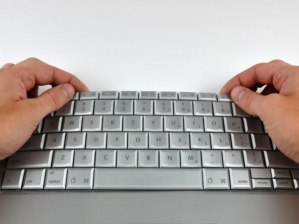 Bow the keyboard out slightly to release the two tabs near the upper corner on each side of the keyboard.