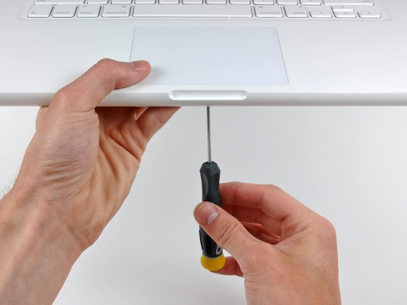 While repeatedly pressing the trackpad to simulate clicking, tighten the T6 Torx set screw until the trackpad no longer wiggles freely.