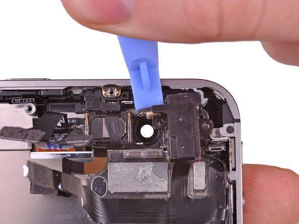 Use a plastic opening tool to start to pry the headphone jack out of its recess in the rear case.