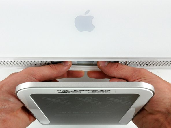 Image 1/2: To lift the front bezel off the iMac, simultaneously: