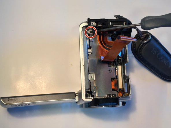 Remove the two 4mm Phillips #00 screws from the underside of the camera.