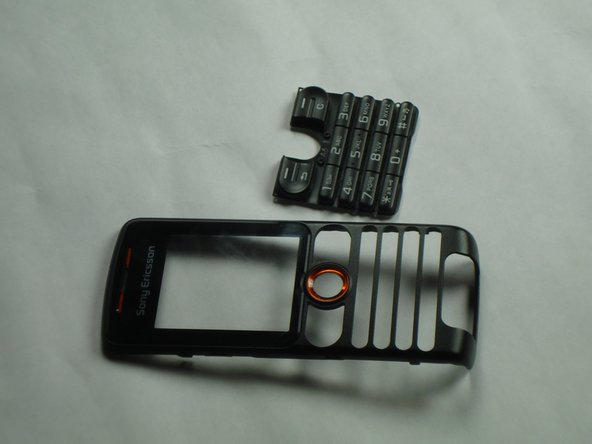 Using the plastic opening tool, press down anywhere on the keypad to separate it from the front case.