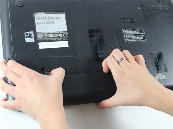 With hand still pushing the left switch, grab onto notch at the center of the two switches.
