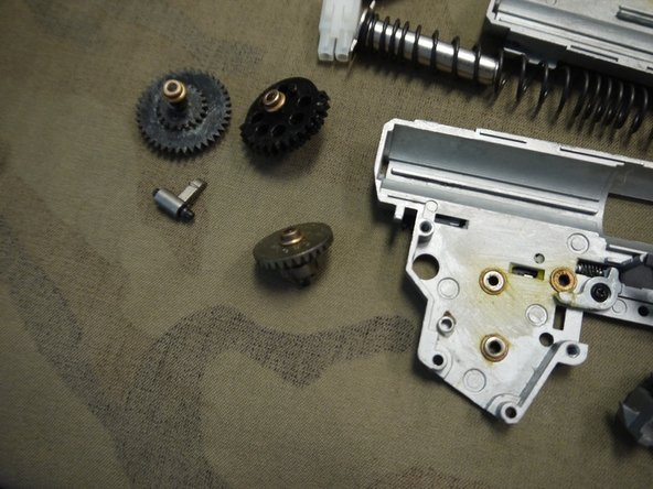 Remove the three gears and the anti-reversal latch. Be careful not to misplace any of the shims or bushings, or the anti-reversal latch spring.