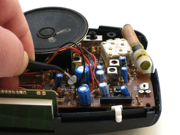 Use the tweezers to grab the softened hot melt glue. Pull the hot melt glue off of the clock radio.