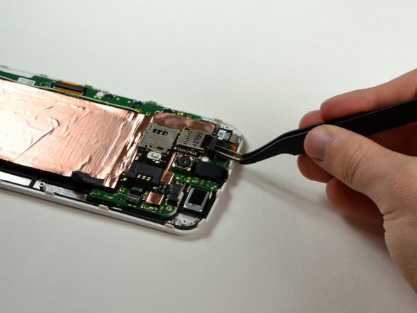 Using a plastic opening tool or tweezers, disconnect the SIM/SD card reader at the top of the phone.