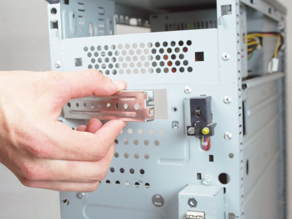 Remove the external drive faceplate by removing the 2 Torx T15 Screws