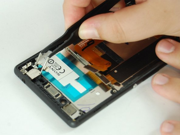 With your fingers, or nylon spudger if necessary, remove headphone jack fastening cover, casing, and sticker.