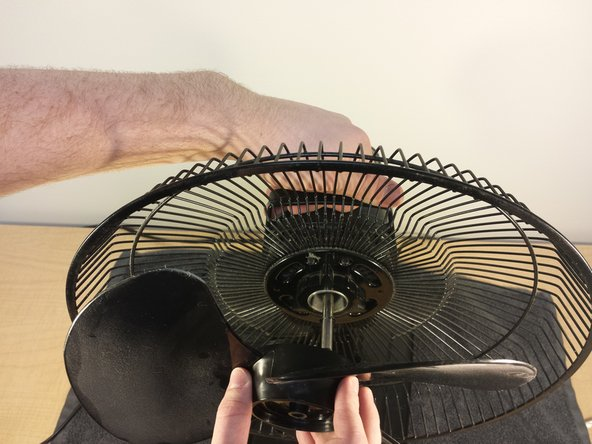 Pull the blade piece straight off the rotor, using your other arm to weigh down the rest of the fan.