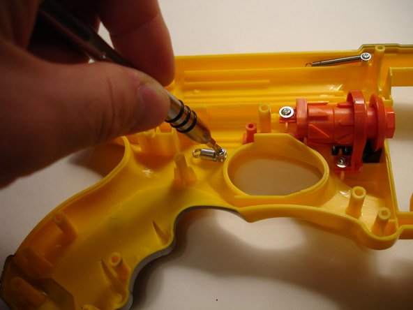 The trigger's spring also attaches via a Phillips screw. A couple of twists with the screwdriver and it comes right out.